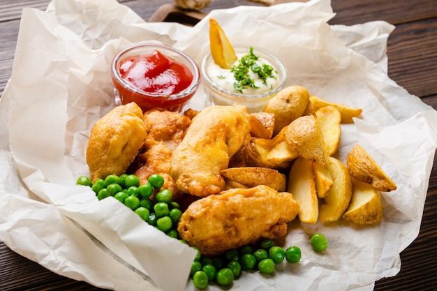 Close-up of british traditional fast food fish and chips with assorted dips, peas, on paper, rustic brown wooden background.