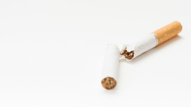 Close-up of broken cigarette on white backdrop