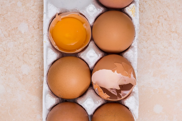 Close-up of broken eggs in white carton on texture backdrop