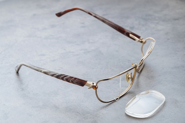 Close up of broken eyeglasses with damaged frame and lens lying on table in optical store