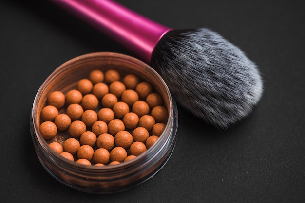 Close-up of bronzing pearls and makeup brush on black surface