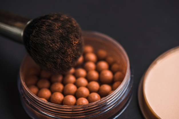 Close-up of bronzing pearls and makeup brush