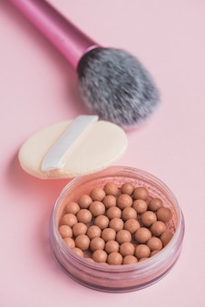 Close-up of bronzing pearls; sponge and makeup brush