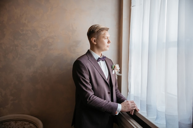 Close up. brooding groom standing near the window. photo with copy space