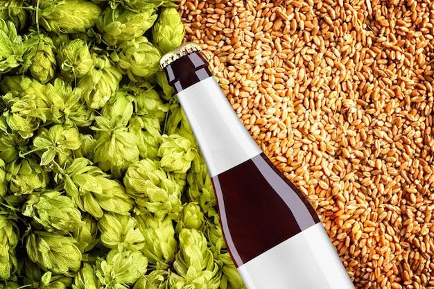 밀 곡물 및 홉 배경에 대각선 배치 bottlle와 갈색 맥주 모형을 닫습니다. 유리에 회색 라벨 조각이 있습니다. 쇼케이스를위한 tempalte 준비.