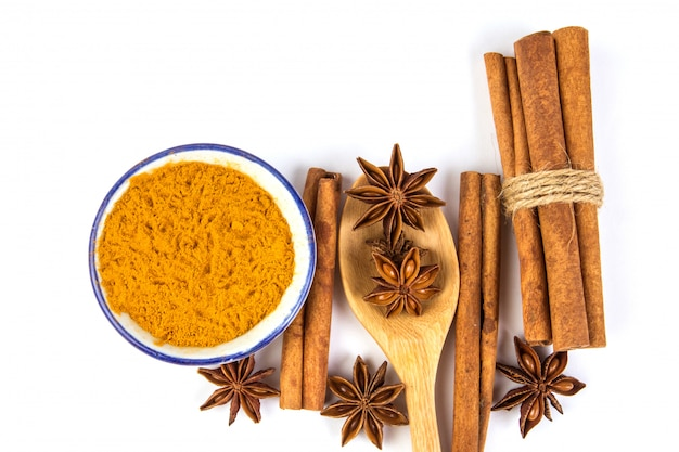 Close up the brown cinnamon stick and powder with star anise spice in wooden spoon isolated on white