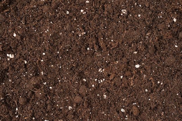 Закройте вверх текстуры почвы коричневого цвета для фона или дизайна, используйте текстурированную поверхность земли в качестве фона