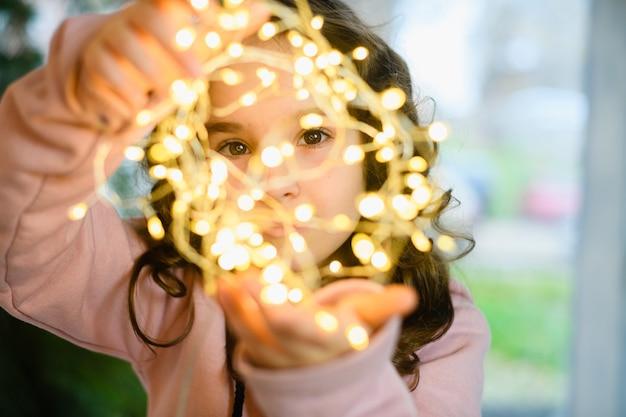빛나는 크리스마스와 새해 화환 조명, 겨울 방학 마법의 분위기를 통해 보는 미취학 아동의 갈색 눈을 닫습니다