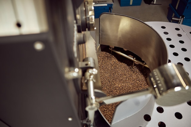 Close up of brown freshly roasted coffee beans resting in special equipment