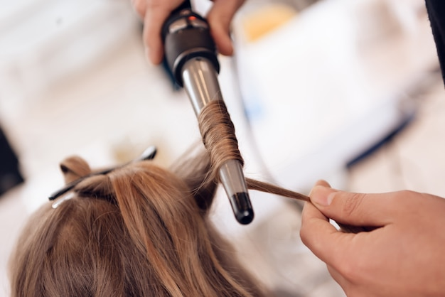 Close up. brown hair woman does curling hair in beauty salon