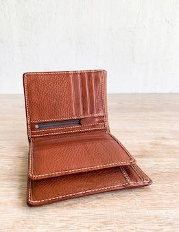 Закройте коричневый кожаный роскошный кошелек на фоне деревянного стола