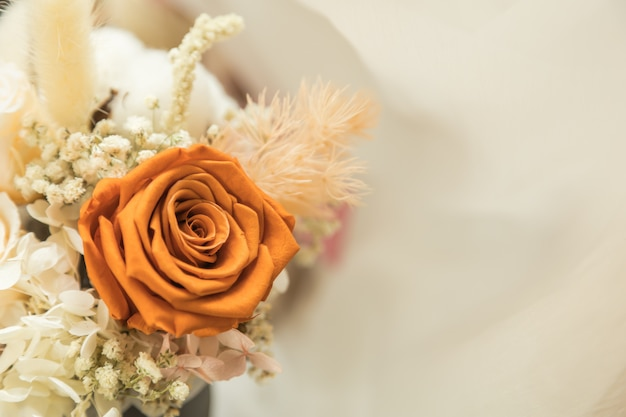 Close up of brown orange roses flower bouquet on white with copyspace.