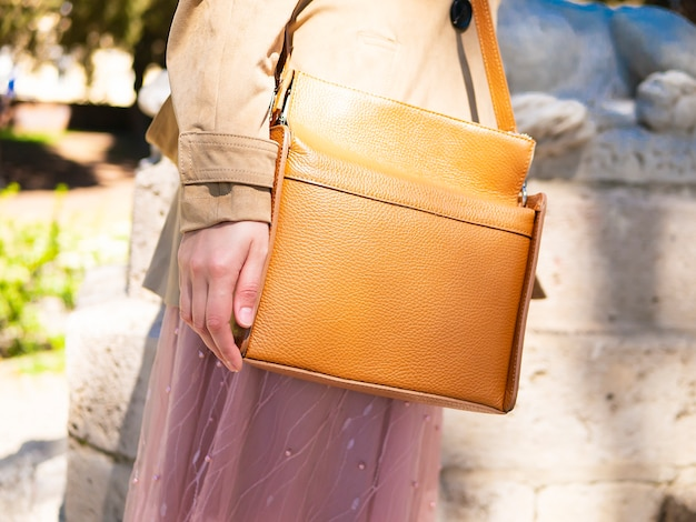 Close up of brown orange stylish bag. elegant, trendy outfit.