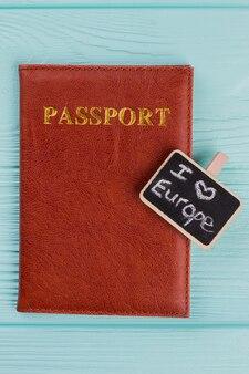 青い机の上に小さな黒板で茶色のパスポートを閉じます。私は黒板でヨーロッパが大好きです。