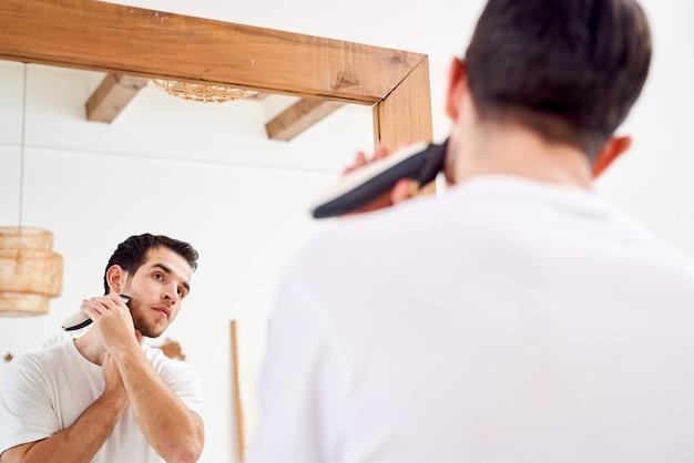 Крупным планом брюнет мужчина в белой футболке бреется, стоя возле зеркала в ванне утром
