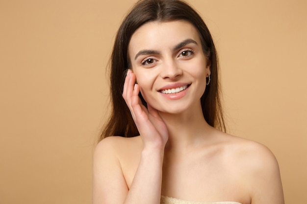 Закройте вверх полуголой женщины 20-х годов с идеальной кожей, рукой на щеке, изолированной на бежевой пастельной стене, портрете. концепция косметических процедур здравоохранения ухода за кожей. .