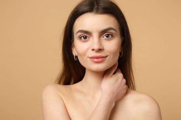 Закройте вверх полуголой женщины 20-х годов с идеальной кожей, рукой на шее, изолированной на бежевой пастельной стене, портрете. концепция косметических процедур здравоохранения ухода за кожей. .