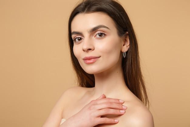 Закройте вверх по полу обнаженной женщины 20-х годов с идеальной кожей на плече, изолированной на бежевом пастельном настенном портрете. концепция косметических процедур здравоохранения ухода за кожей.