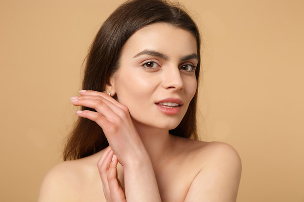 Close up brunette half naked woman 20s with perfect skin, nude make up isolated on beige pastel wall, portrait. skin care healthcare cosmetic procedures concept.
