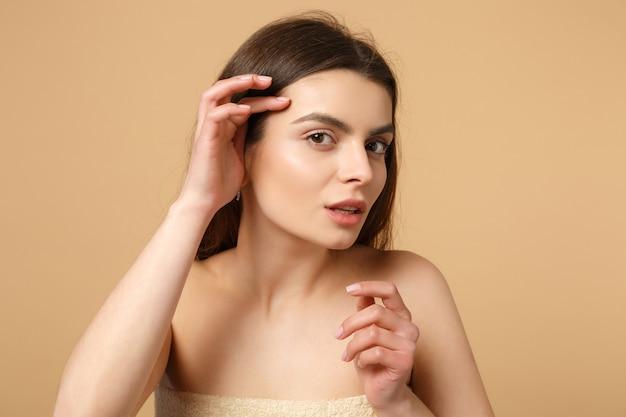 완벽한 피부와 갈색 머리 반 벌거 벗은 여자 20 대를 닫습니다, 누드 메이크업은 베이지 색 파스텔 벽, 초상화에 격리됩니다. 스킨 케어 의료 화장품 절차 개념.