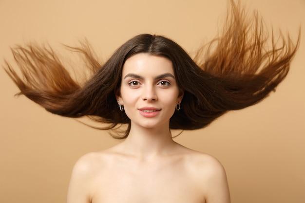 Крупным планом брюнетка полуголая женщина 20-х годов с идеальной кожей, обнаженный макияж, изолированные на бежевой пастельной стене, портрет. концепция косметических процедур здравоохранения ухода за кожей.