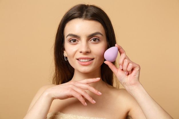 完璧な肌、ベージュのパステルカラーの壁、肖像画に分離されたヌードメイクでブルネットの半分裸の女性20代を閉じます。スキンケアヘルスケア美容手順の概念。