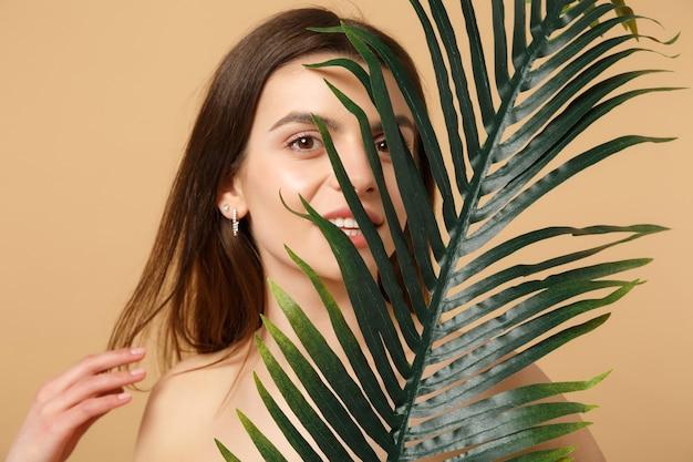 베이지 색 파스텔 벽에 고립 된 완벽한 피부, 누드 메이크업 및 팜 리프와 갈색 머리 반 벌거 벗은 여자를 닫습니다