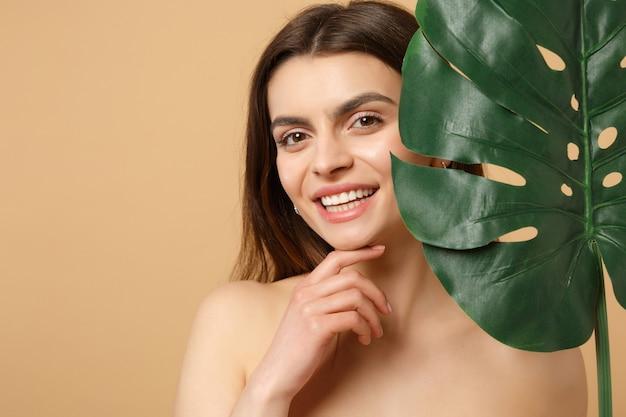 完璧な肌、ヌードメイク、ベージュのパステルカラーの壁に分離されたヤシの葉を持つブルネットの半分裸の女性をクローズアップ