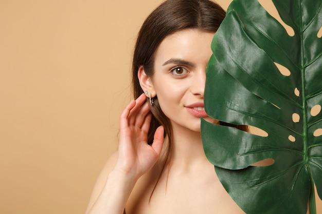 Крупным планом полуобнаженная брюнетка с идеальной кожей, обнаженным макияжем и пальмовым листом на бежевой пастельной стене