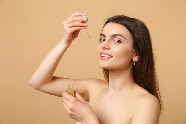 Primo piano donna mezza nuda bruna con pelle perfetta, trucco nudo applicare olio dalla bottiglia sul viso isolato su muro beige pastello