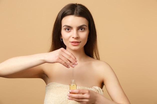 완벽한 피부와 갈색 머리 반 벌거 벗은 여자를 닫습니다, 누드 메이크업은 베이지 색 파스텔 벽에 고립 된 얼굴에 병에서 기름을 적용