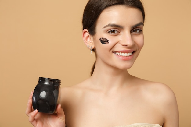 Close up brunette half naked woman with perfect skin, nude make up black mask isolated on beige pastel wall