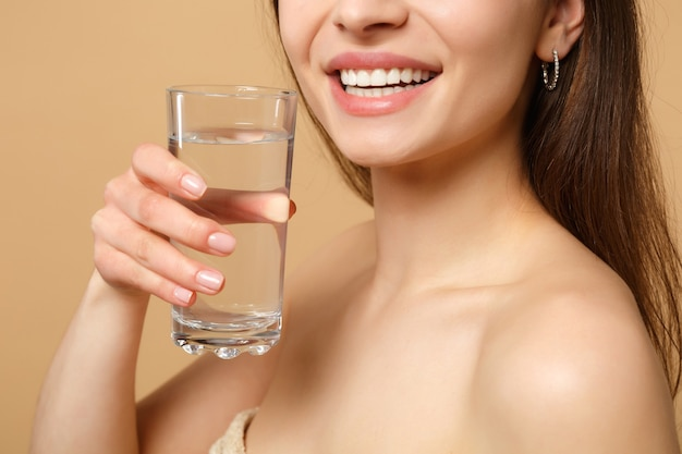 Close up brunette half naked woman with perfect skin nude make up glass water isolated on beige pastel wall