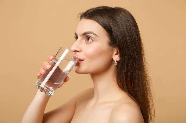 베이지 색 파스텔 벽에 고립 된 완벽한 피부 누드 메이크업 유리 물과 갈색 머리 반 벌거 벗은 여자를 닫습니다