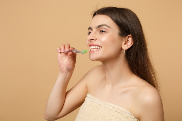 Close up brunette half naked woman with perfect skin, nude make up hold brush isolated on beige pastel wall