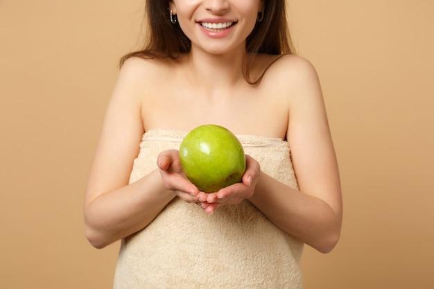 Close up bruna mezza donna nuda con una pelle perfetta, trucco nudo tiene mela isolata sul muro beige pastello