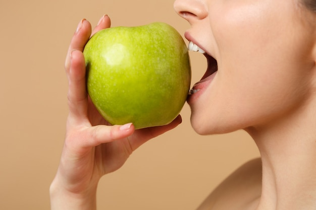 Close up brunette half naked woman with perfect skin, nude make up holds apple isolated on beige pastel wall