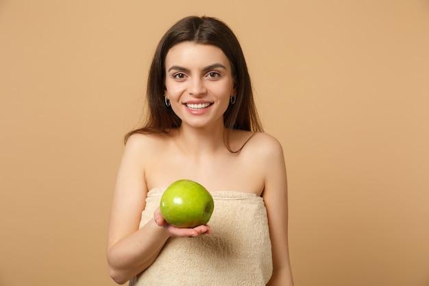 완벽한 피부와 갈색 머리 반 벌거 벗은 여자를 닫습니다, 누드 메이크업은 베이지 색 파스텔 벽에 고립 된 사과를 보유하고 있습니다.
