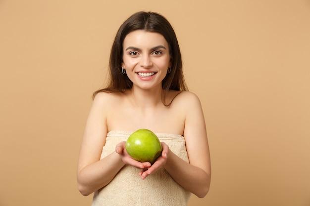 完璧な肌を持つブルネットの半分裸の女性をクローズアップ、ヌードメイクはベージュのパステルカラーの壁に分離されたリンゴを保持します