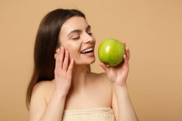 Крупным планом брюнетка полуобнаженная женщина с идеальной кожей, обнаженный макияж держит яблоко, изолированное на бежевой пастельной стене