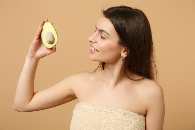 Close up brunette half naked woman with perfect skin nude make up holds avocado isolated on beige pastel wall