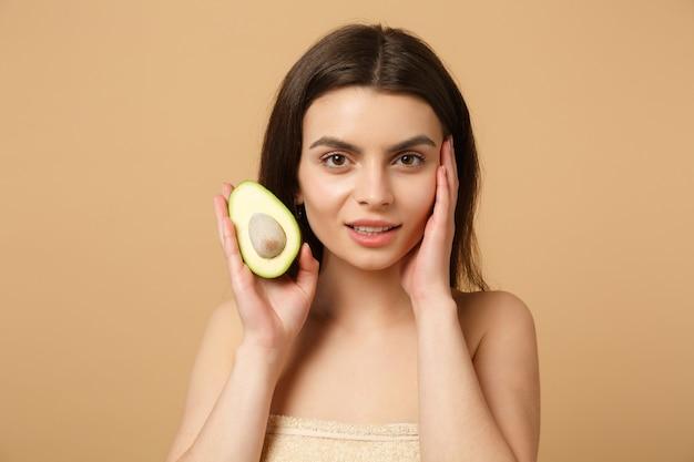 Close up bruna mezza donna nuda con pelle perfetta trucco nudo tiene avocado isolato su muro beige pastello