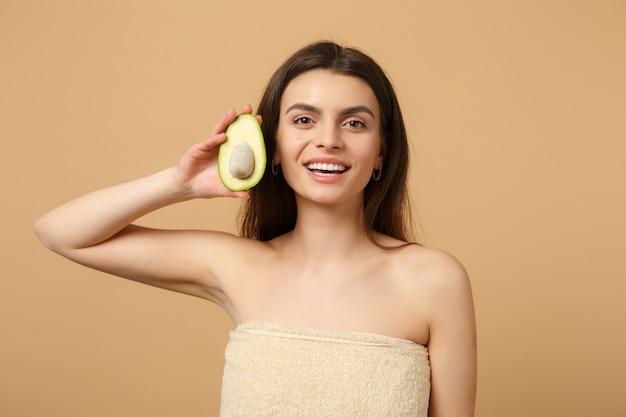 Крупным планом полуобнаженная брюнетка с идеальной кожей обнаженного макияжа держит авокадо, изолированное на бежевой пастельной стене