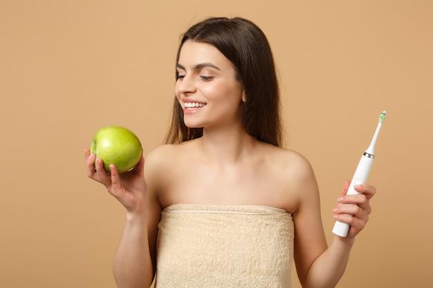 完璧な肌を持つブルネットの半分裸の女性をクローズアップ、ヌードメイクはベージュのパステルカラーの壁に分離されたブラシを保持します