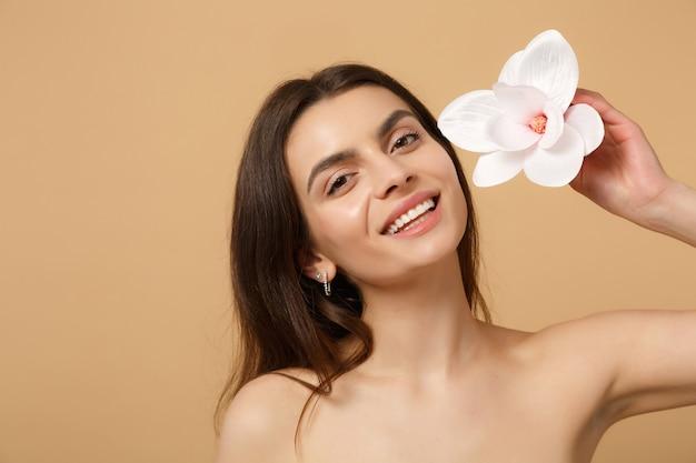 Close up bruna mezza donna nuda con una pelle perfetta, trucco nudo isolato su muro beige pastello