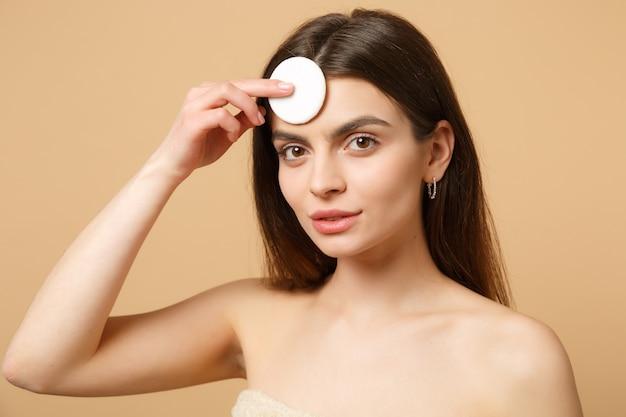 Крупным планом брюнетка полуобнаженная женщина с идеальной кожей, обнаженный макияж, изолированные на бежевой пастельной стене