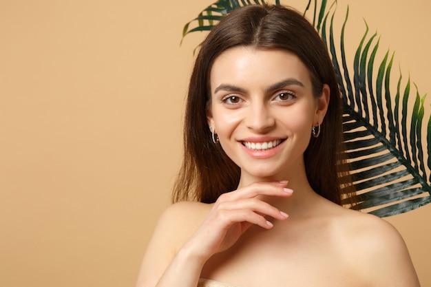 Close up bruna mezza donna nuda con pelle perfetta, trucco nudo e foglia di palma isolata sul muro beige pastello