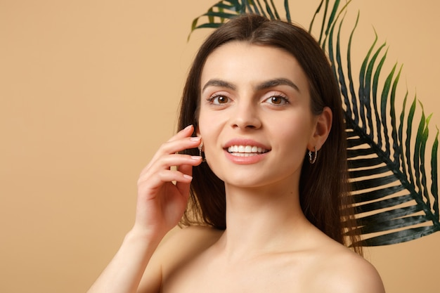 Close up brunette half naked woman with perfect skin, nude make up and palm leaf isolated on beige pastel wall