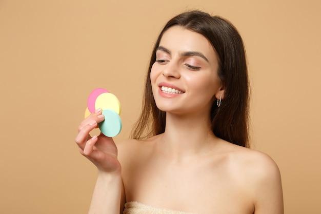 Close up bruna mezza donna nuda con una pelle perfetta, rimuovendo il trucco nudo isolato su muro beige pastello