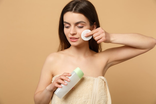 Крупным планом полуобнаженная брюнетка с идеальной кожей, снимающая обнаженный макияж, изолирована на бежевой пастельной стене